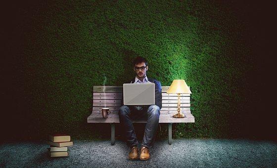 Muz sediaci s laptopom na lavicke